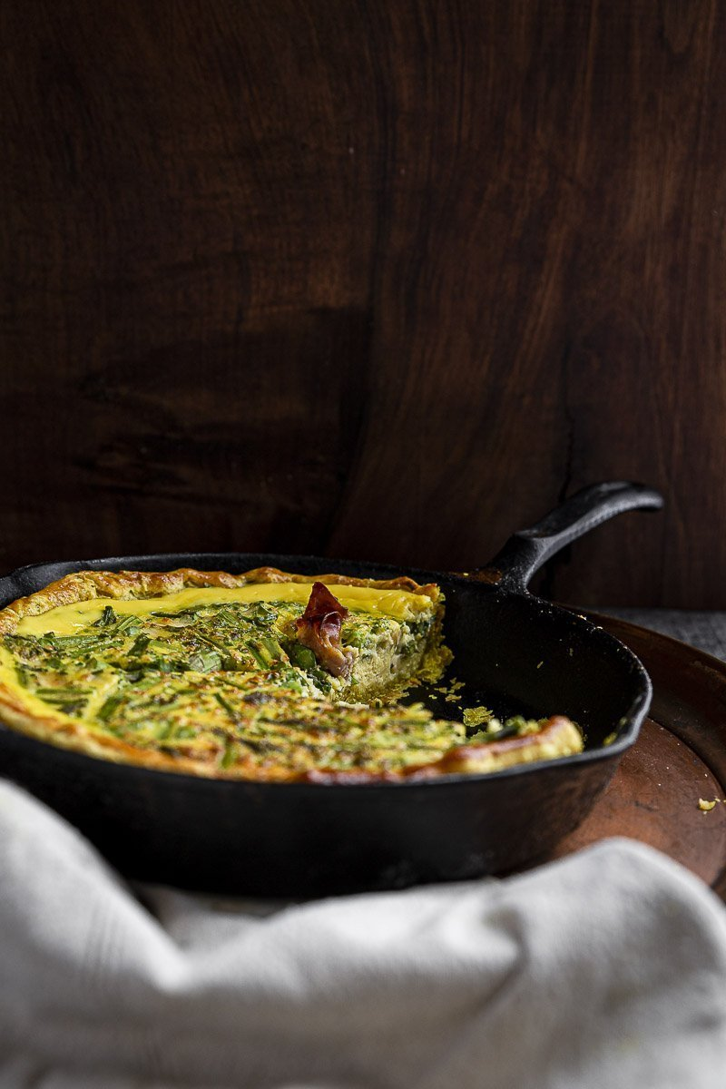 asparagus quiche baked in a cast iron skillet with one slice removed