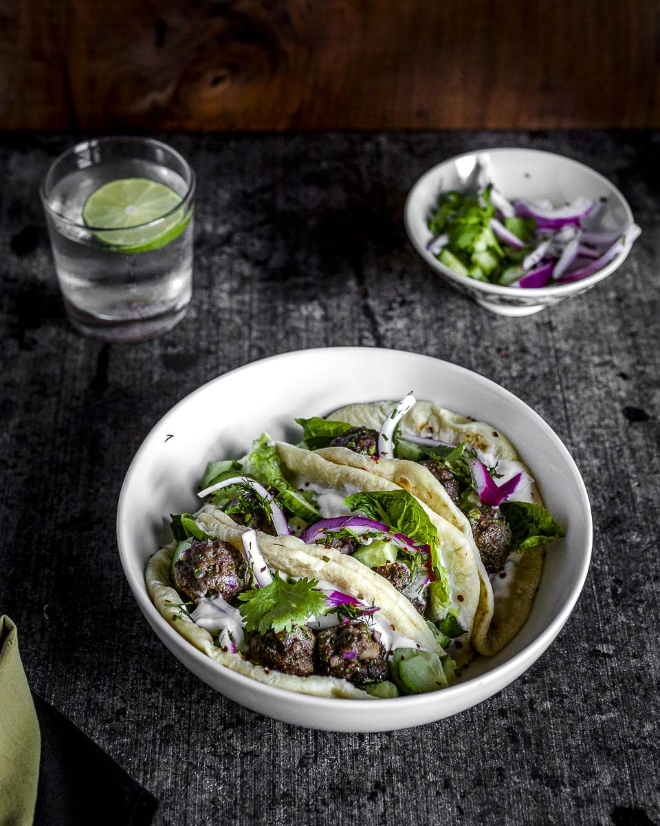 three meatball flour tortilla soft tacos in a white bowl topped with yogurt sauce, pickled red onion, lettuce, and cucumber