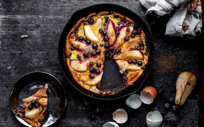 pear blueberry clafoutis baked in a cast iron pan
