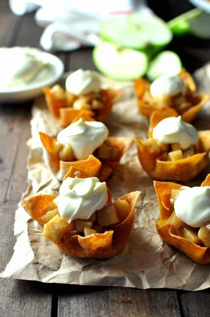 Six Mini Apple Pies made with wonton cups with a dollop of cream.