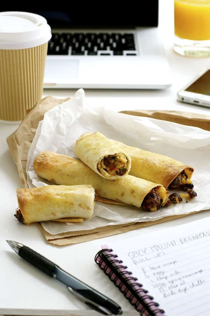 Spicy Italian Breakfast Roll Ups on a work desk with takeaway coffee cup, computer and notebook