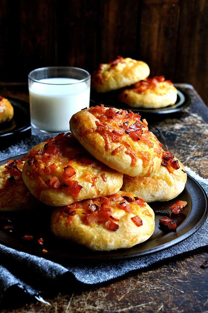 A pile of Double Cheese and Bacon Rolls with a glass of milk in the background