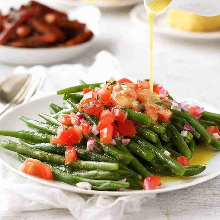 Pouring lemon dressing over green bean salad