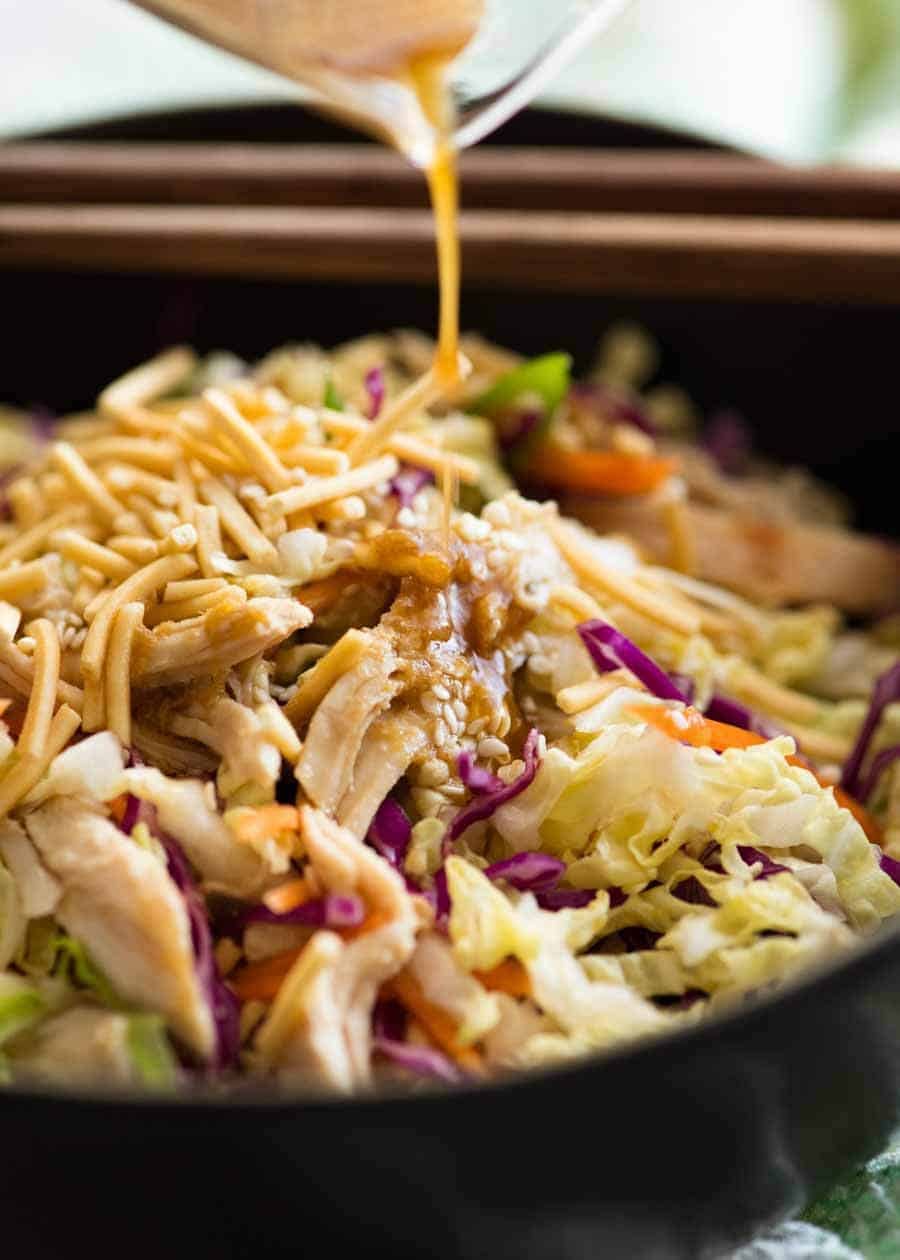 Asian Dressing being poured over Chinese Chicken Salad