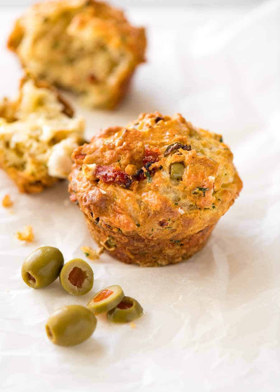 Savoury Cheese Muffins with Sun Dried Tomatoes, Feta and Olives on white paper, with olives on the side, ready to be eaten.