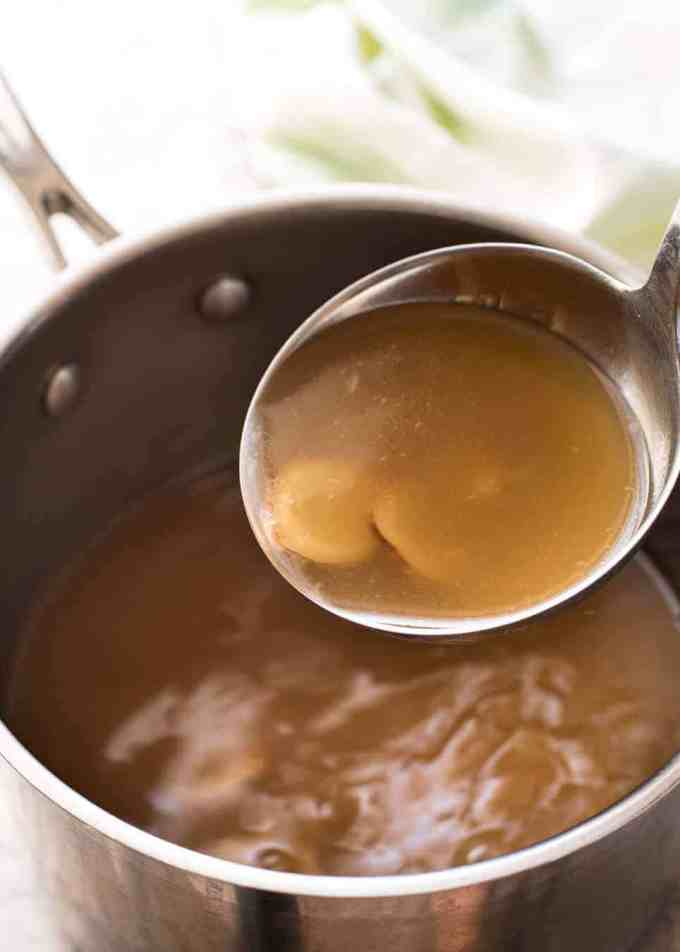 A ladle scooping up Chinese Noodle Soup broth with ginger and garlic.
