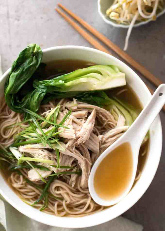 Chinese noodle soup with chicken, bok choi and noodles in a white bowl.