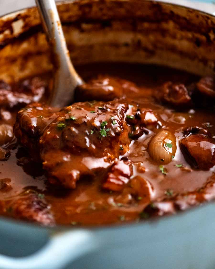 Serving freshly cooked Coq au Vin - French chicken stew