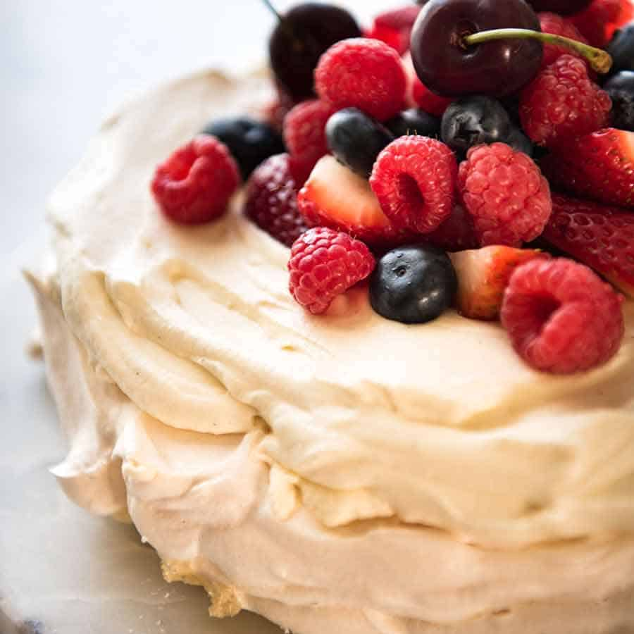 Close up of Pavlova topped with cream and berries