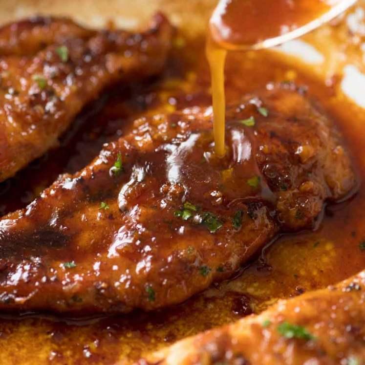 Close up of Honey Garlic Sauce being drizzled over Honey Garlic Chicken