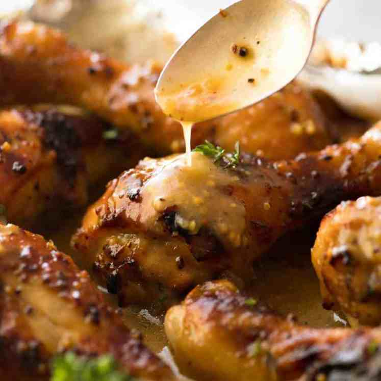 Close up of Honey Mustard sauce being drizzled over Baked Chicken Drumsticks