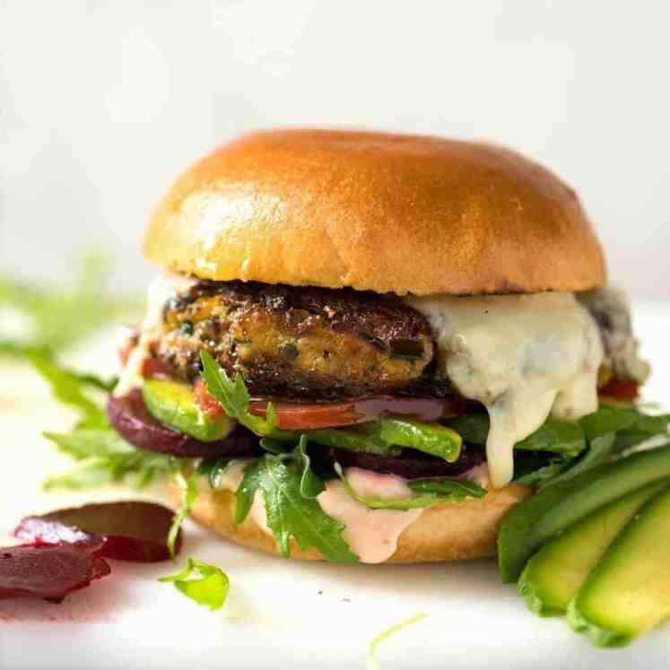 A veggie burger with melted cheese, avocado, beetroot, tomato and lettuce on a soft golden bun.