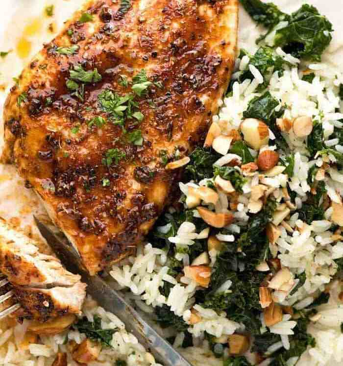 Baked Chicken Breast with a side of Garlic Butter Rice with Kale on a white plate, ready to be eaten.
