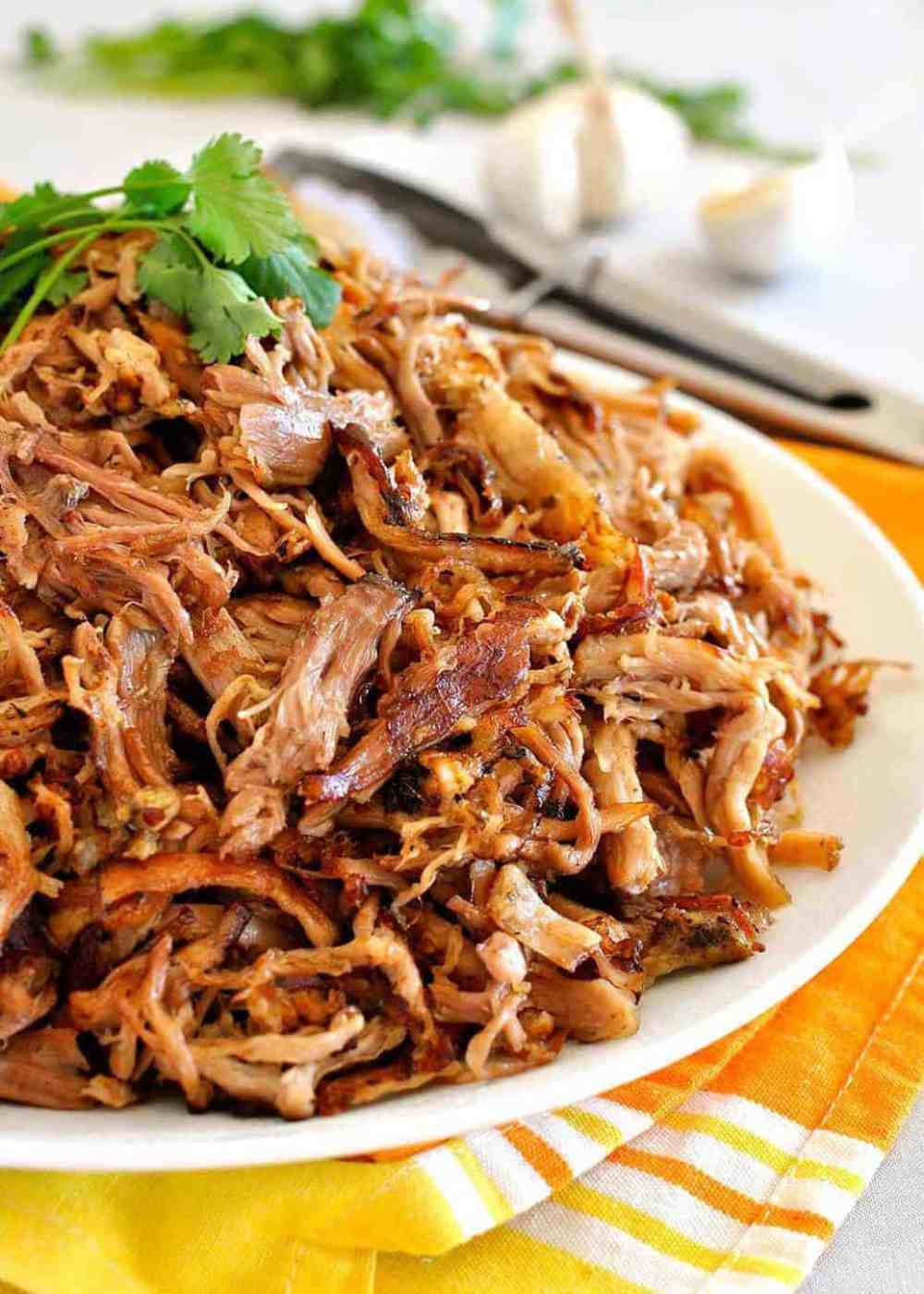 Pile of golden, crispy and juicy Pork Carnitas on a white plate.