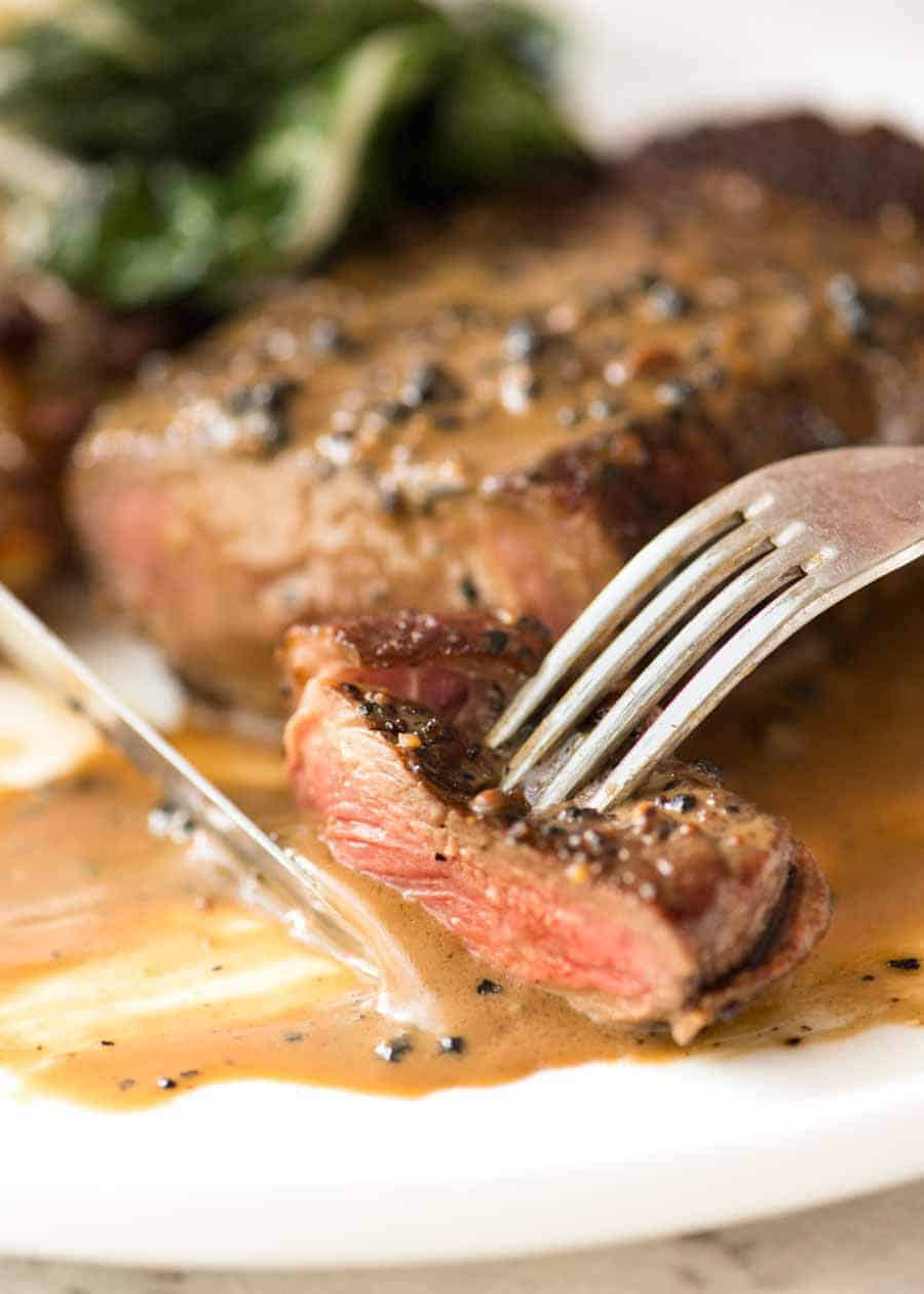 Close up of fork and knife eating a piece of Steak with Creamy Peppercorn Sauce
