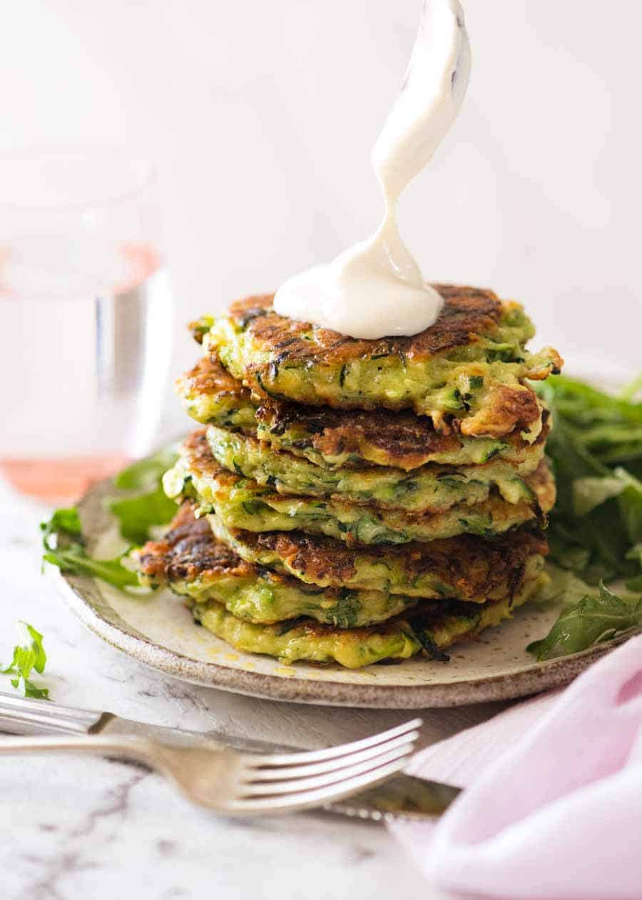Dolloping sour cream on a stack of Crispy Zucchini Fritters