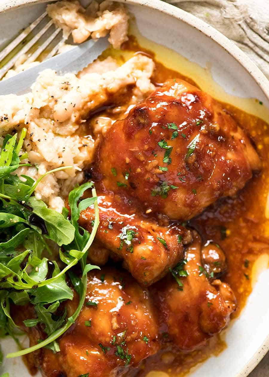 Overhead photo of Sticky Baked Chicken Thighs on a plate with a side of mashed white beans and rocket parmesan salad