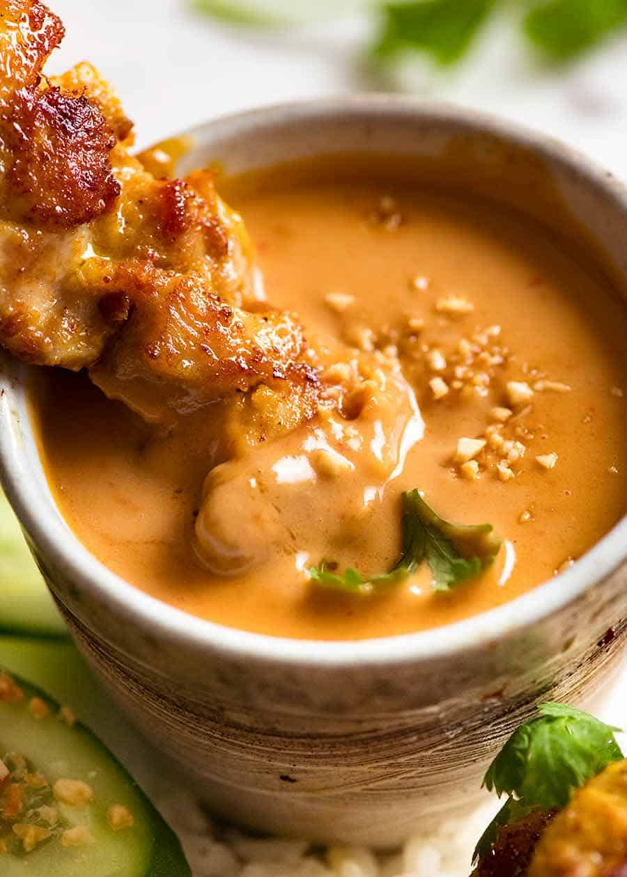 Close up of Thai Chicken Satay being dipped into Thai Peanut Sauce