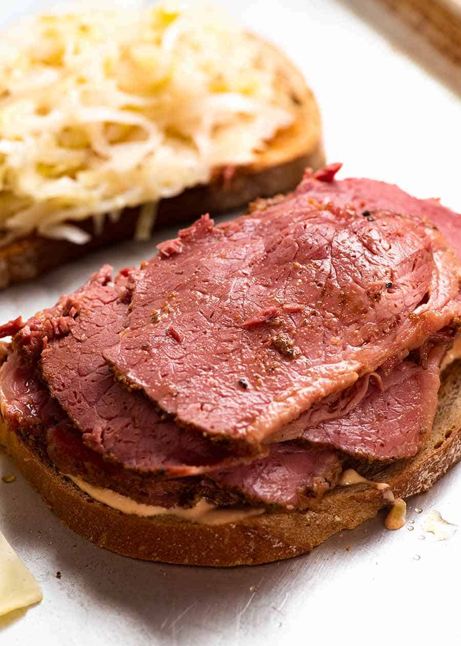 Pastrami being piled onto Reuben Sandwich