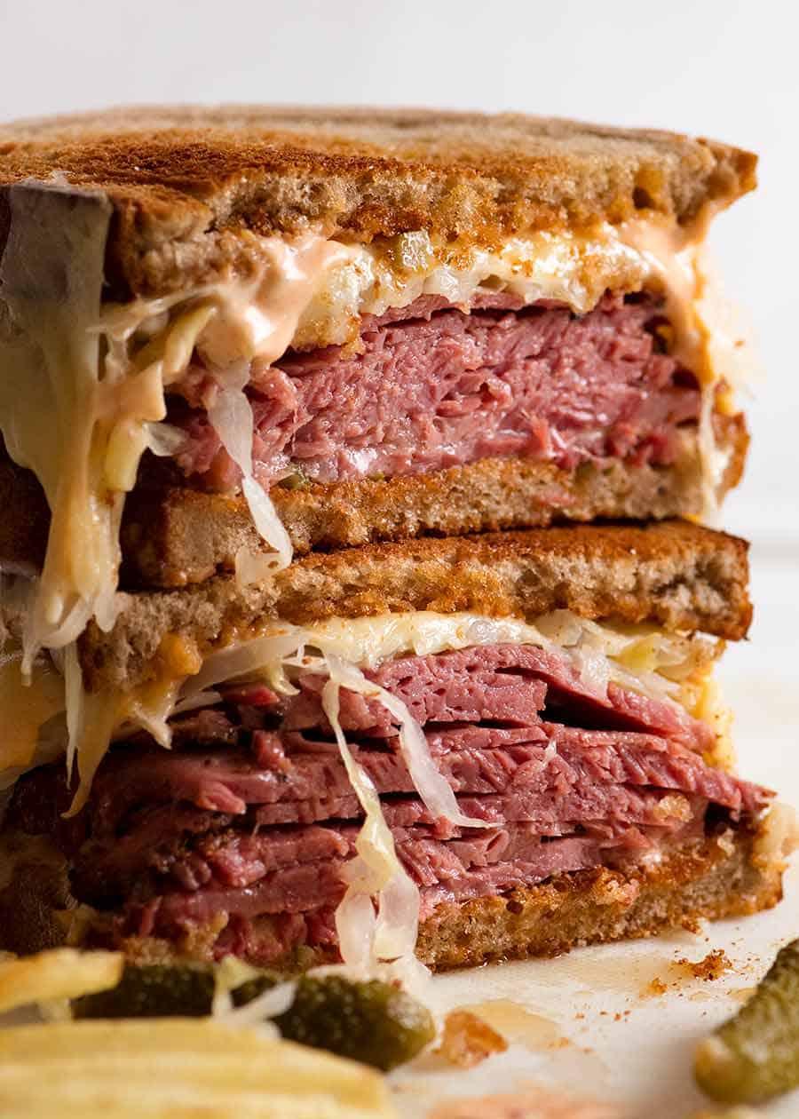 Reuben Sandwich loaded with homemade pastrami, easy quick sauerkraut, Russian Dressing, Swiss cheese on rye bread, ready to be eaten. Katz's deli copycat recipe.