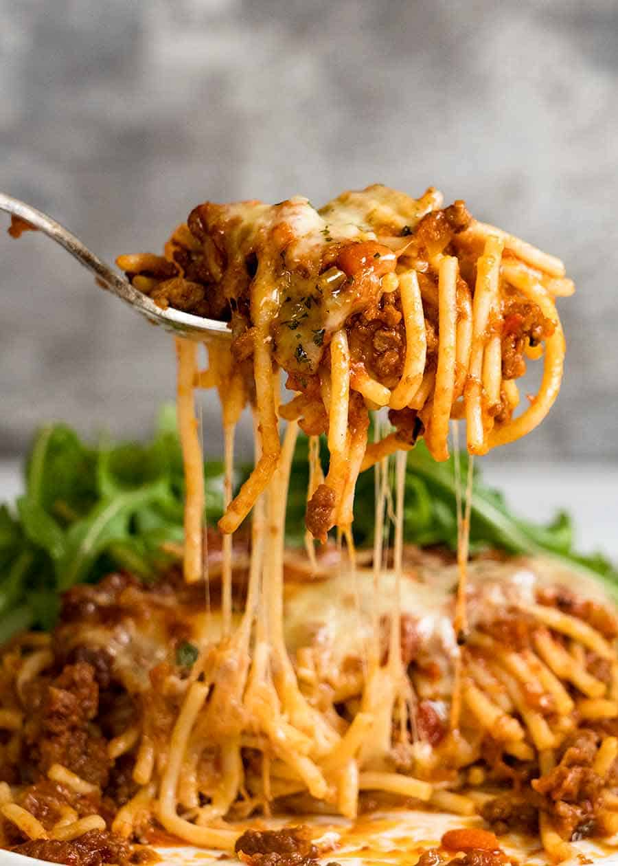 Forking lifting up cheesy Baked Spaghetti