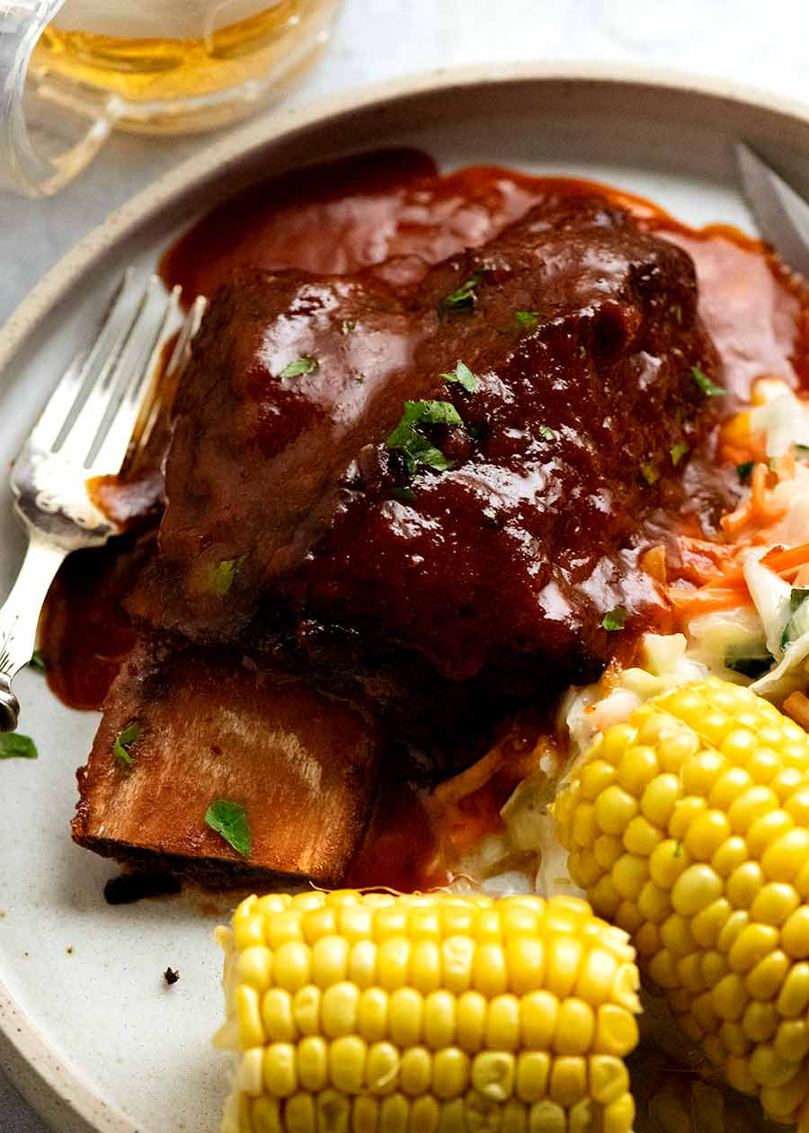 Beef Ribs in barbecue sauce on a plate with coleslaw and corn