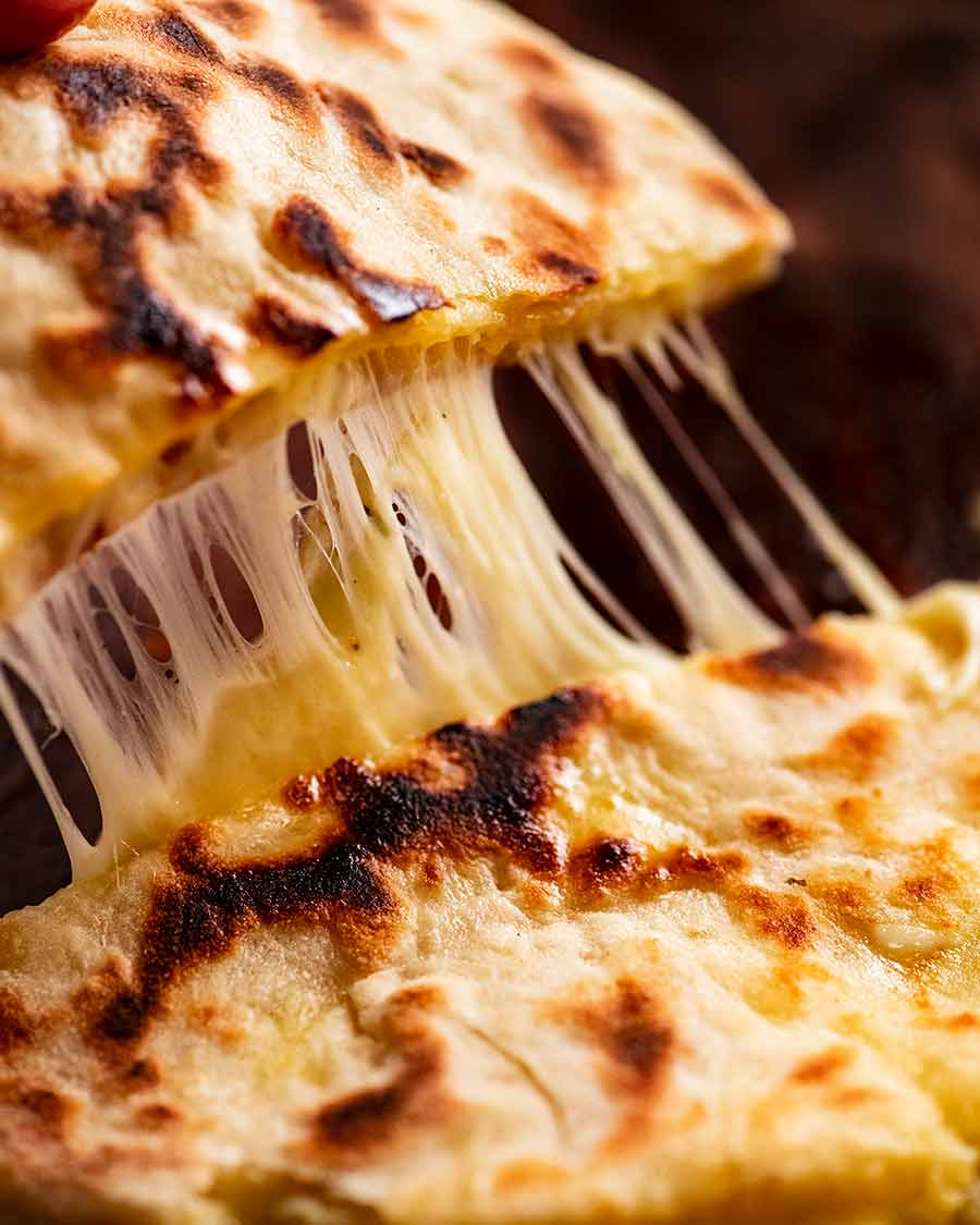 Cheese naan being picked up - cheese pull shot!