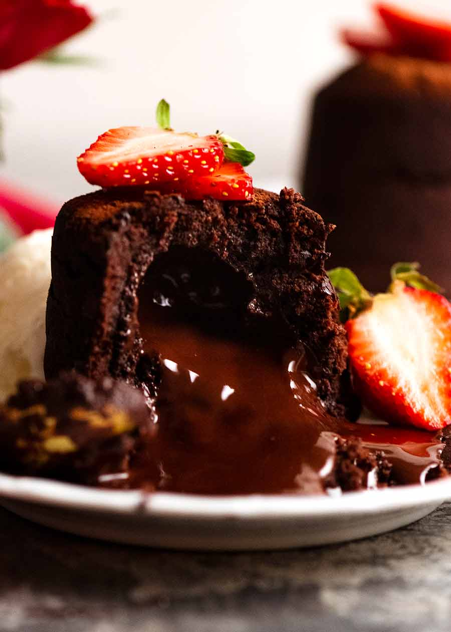 Close up of Molten Chocolate Cake with chocolate lava pouring out, decorated with strawberries