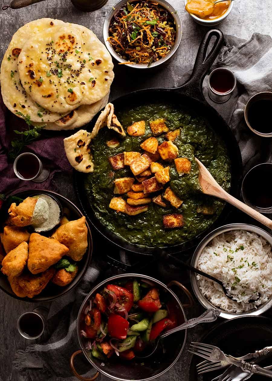 Indian feast menu - Palak Paneer, Basmati rice, homemade naan, samosas and Cabbage Thoran side salad