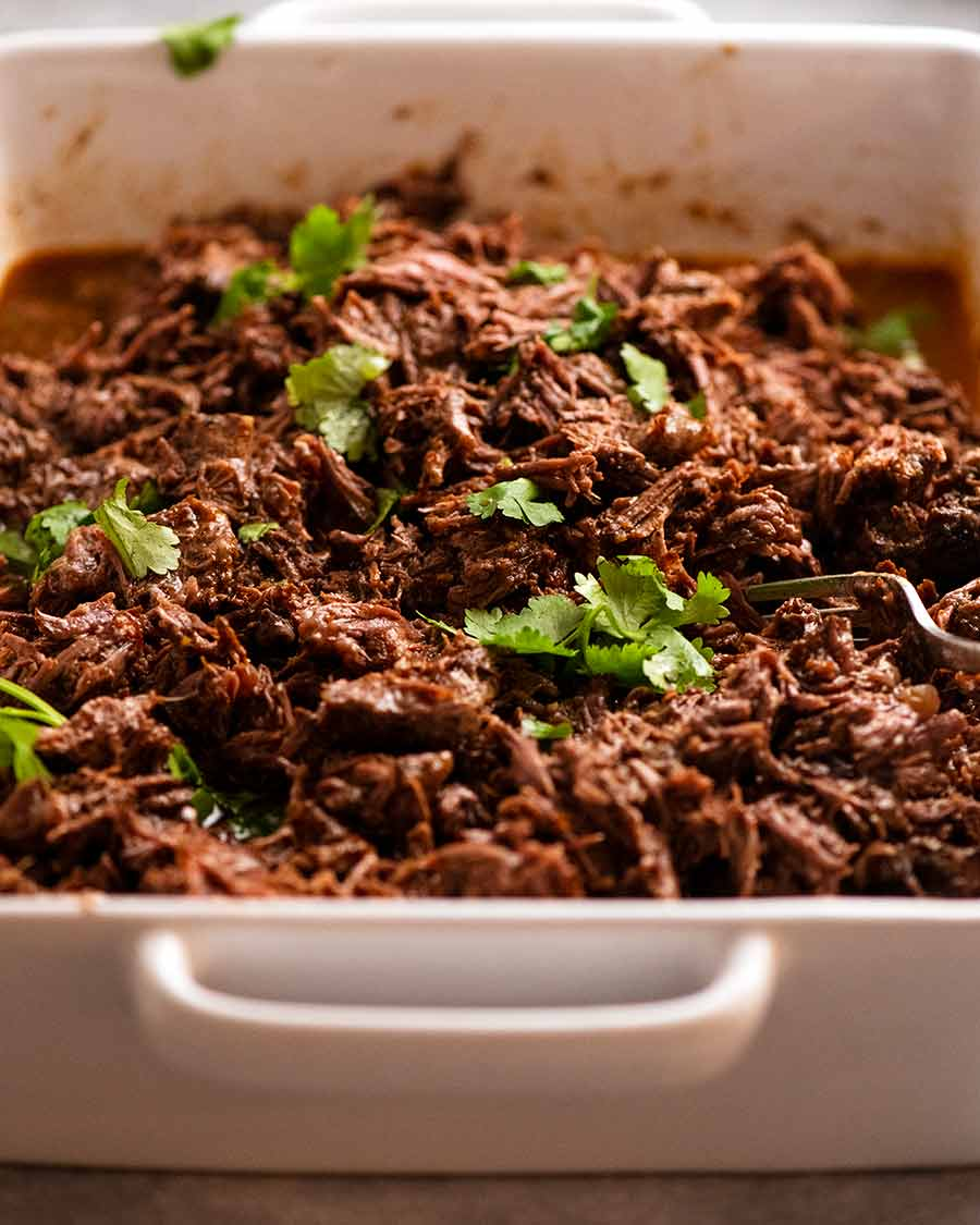 Casserole dish filled with Beef Barbacoa ready to use in tacos and burritos