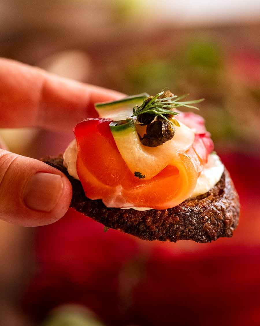 Close up photo of Beetroot Cured Salmon on crispy bead with Horseradish Cream Sauce, Fried Capers and fresh dill