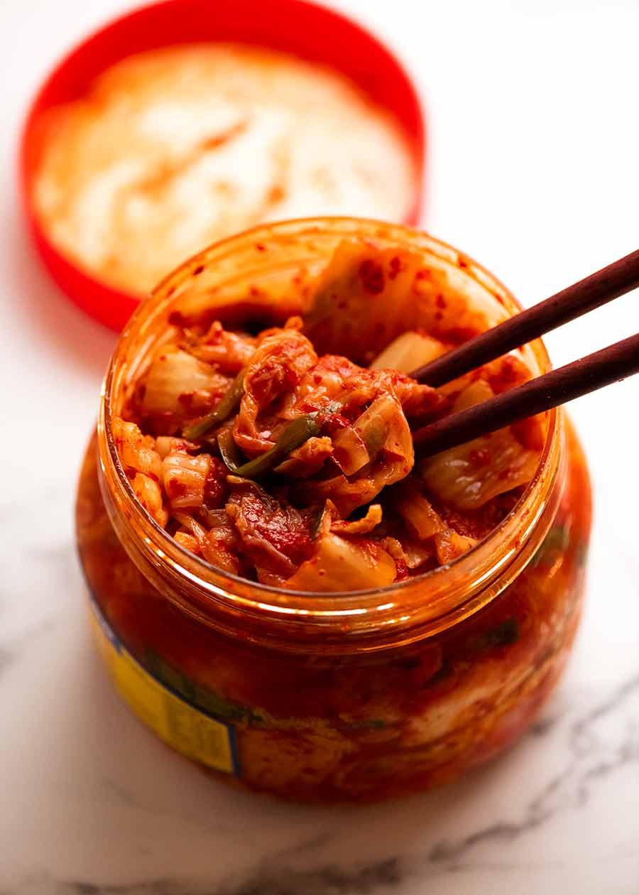 Close up of chopsticks picking up kimchi to make Kimchi Fried Rice