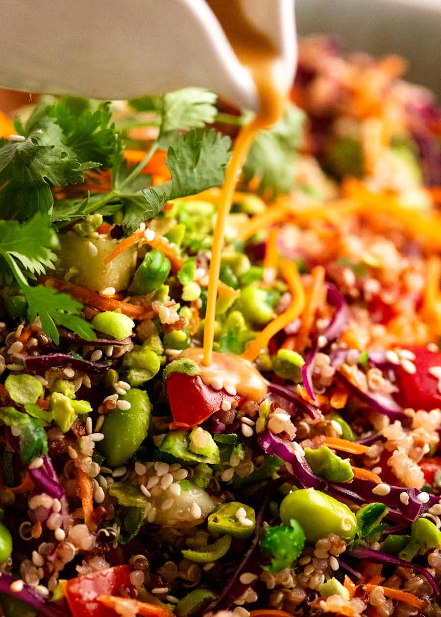 Close up of pouring garlic ginger dressing over Quinoa Salad