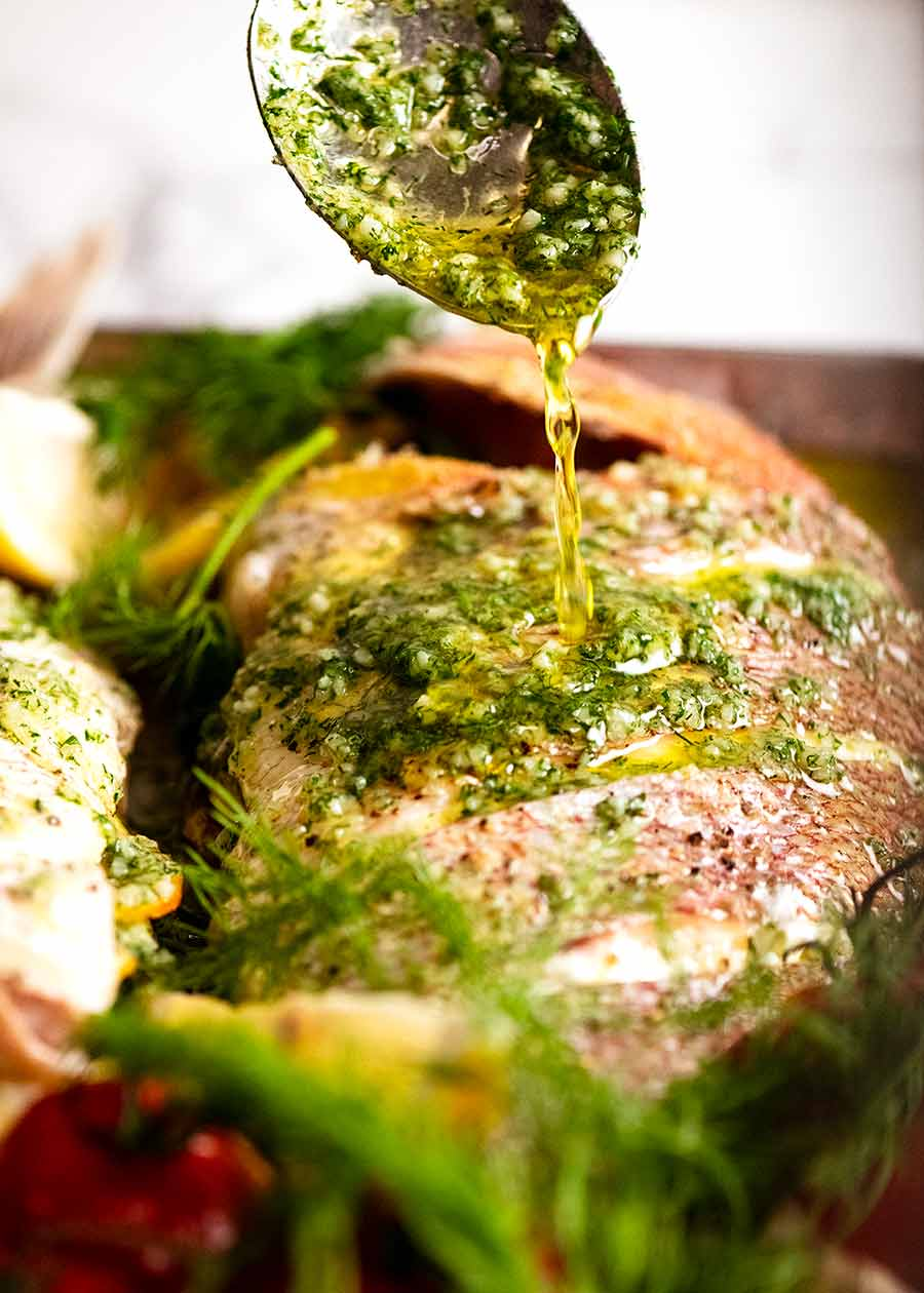 Drizzling garlic dill butter of whole baked snapper