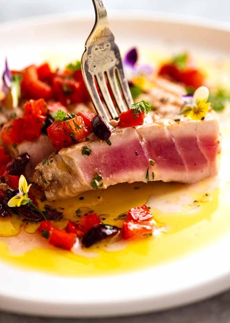 Close up of fork picking up a slice of tuna steak