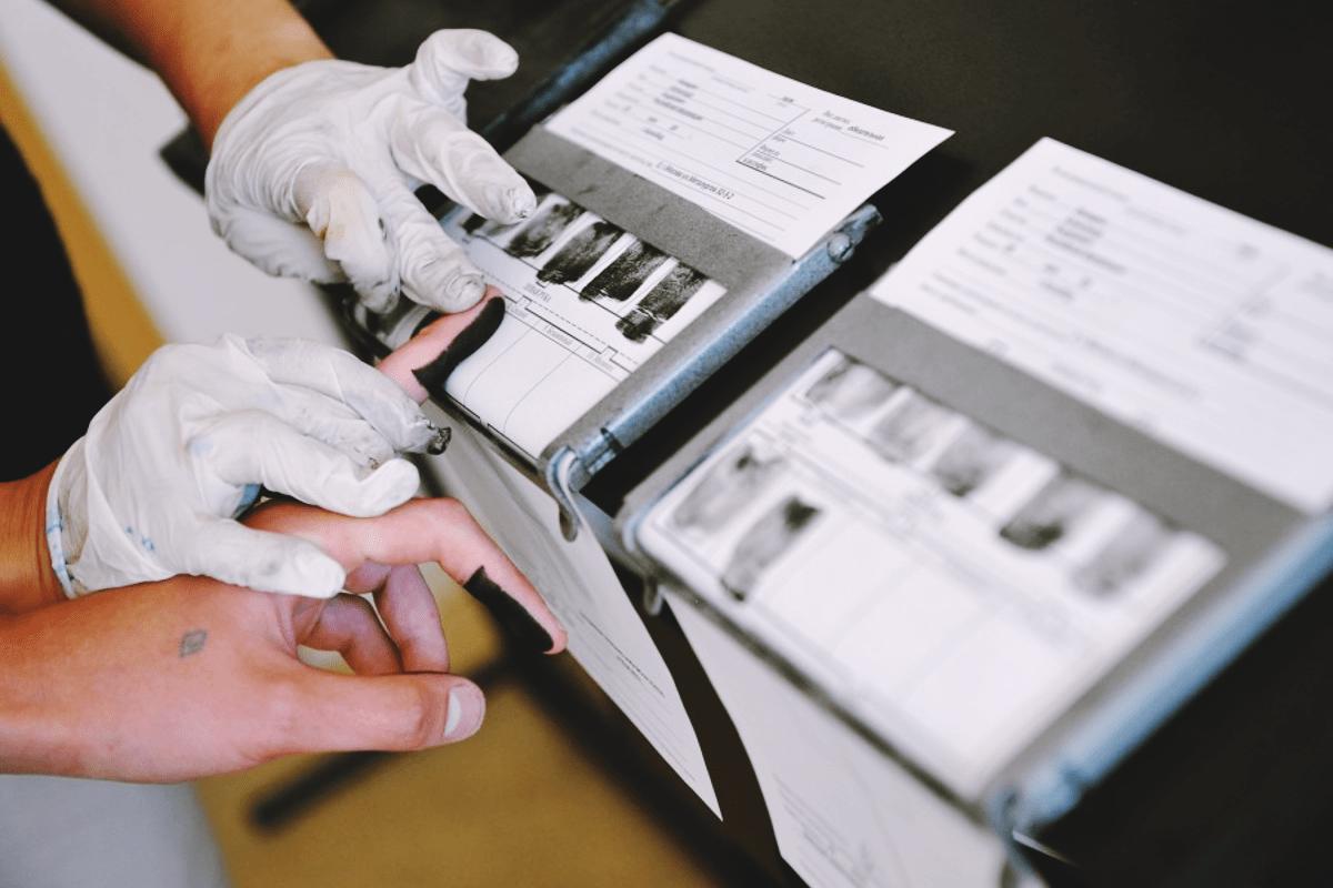 fotografía de una mano poniendo huellas dactilares sobre un papel para formalizar su nacionalidad