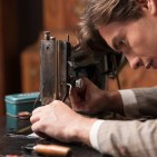 a male worker uses a sewing machine