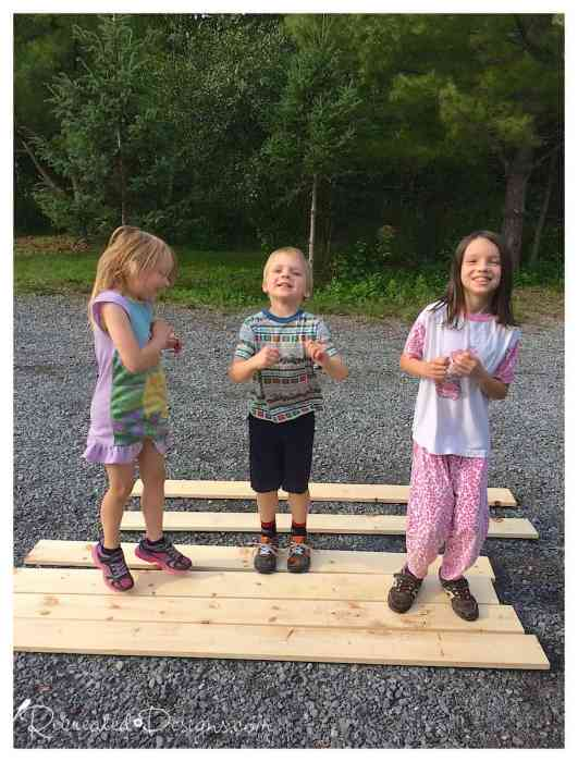 kids jumping on pine boards to rough them up