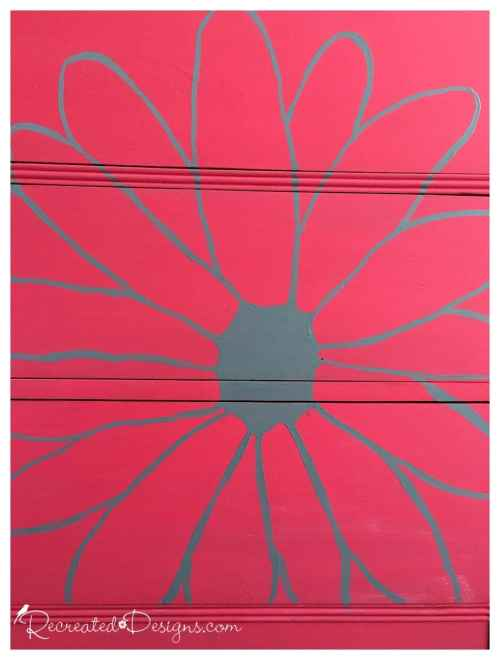 the outline of a large flower on a painted vintage dresser
