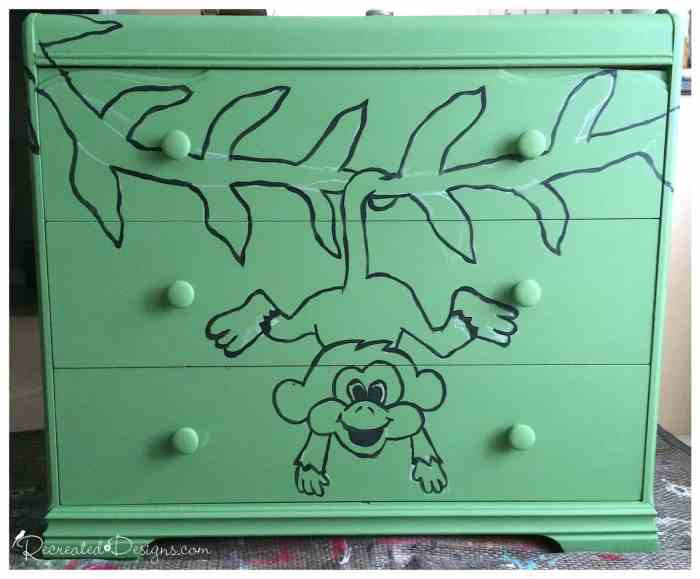 painting a chalked out picture on an antique dresser