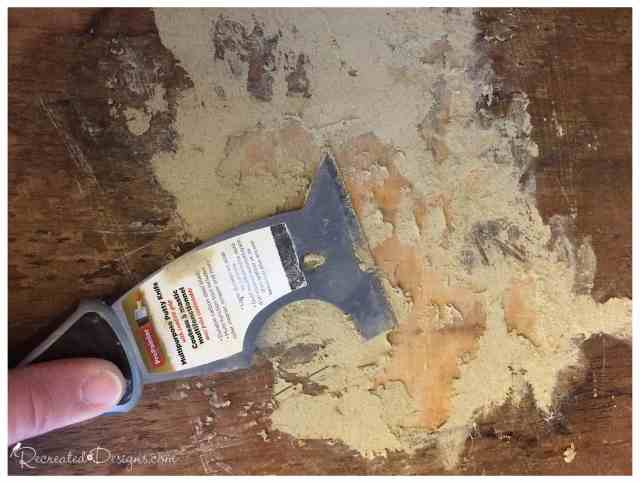 using a putty knife and wood filler to repair an old dresser
