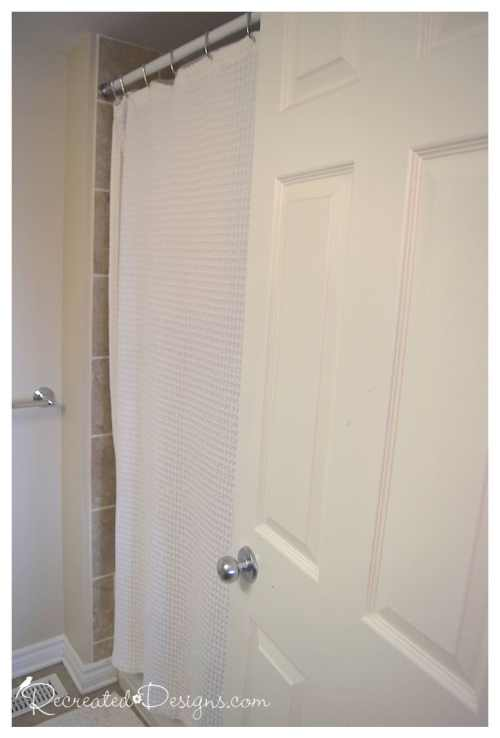 a plain white shower curtain in a bathroom