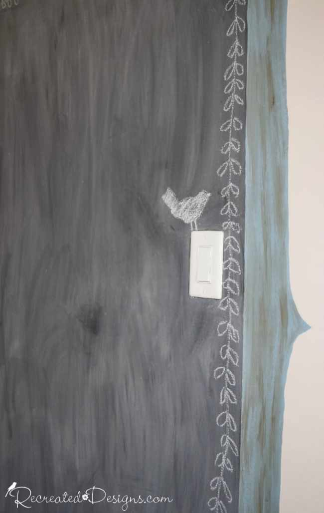a little chalk bird sitting on a light switch plate