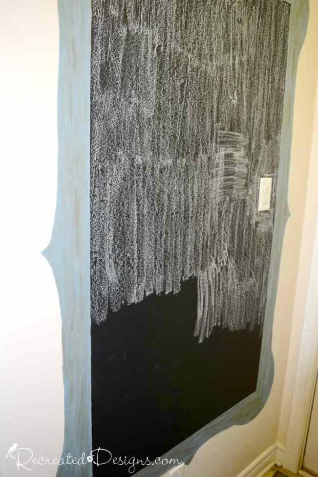 seasoning a newly painted chalkboard on a wall
