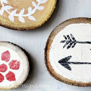 close up of wood slice magents painted with flowers and arrows