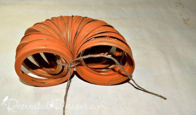 tying mason jar rings together to make a pumpkin