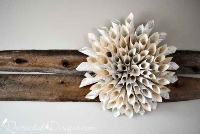 A large book page flower on two salvaged pieces of wood