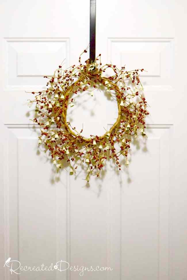 holiday wreath on a door with berries and bells