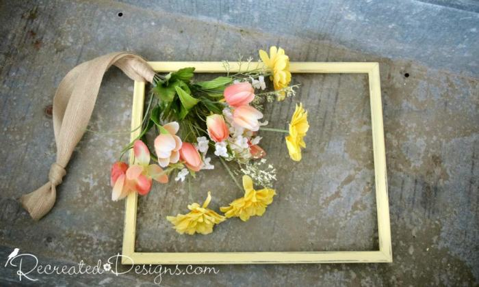 adding flowers to a picture frame to make a wreath
