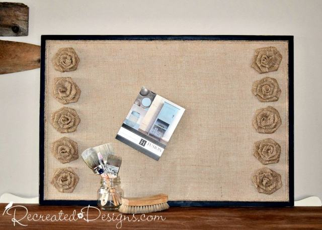 reclaimed cork board covered with burlap and burlap flowers